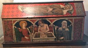 Auf dem Sarg sieht man links Maria Magdalena, in der Mitte Jesus und rechts die heilige Rita.
